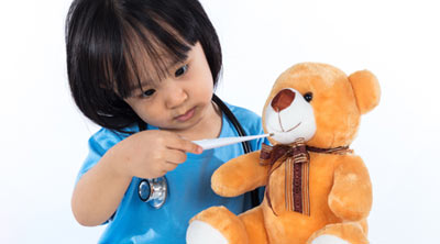 Asian Chinese little girl examine teddy bear with thermometer